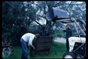 Circa 1994, having recovered the ore car from the New Era mine near Pentz, Butte County, California, Bill, Tom, Scott and John (driving the tractor) unload the ore car at its temporary resting place in Red Bluff.